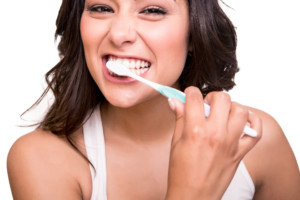 Smiling young woman with healthy teeth holding a tooth brush