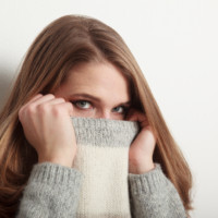 Woman hiding her face in her sweater collar
