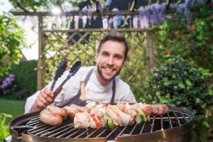 Freundlicher Koch vor Grillfleisch
