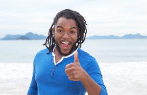 Mann mit Rastalocken am Strand zeigt den Daumen