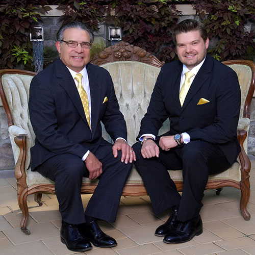 Dr. Kenneth Eye and Dr. Kenneth Eye II sitting together on a sofa, wearing suits and gold ties.