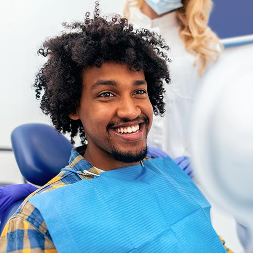 Young male patient smiling in a dental chair after root canal therapy.
