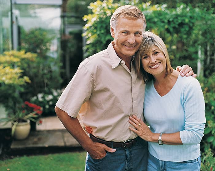 A middle-aged couple smiling with custom-made dental crowns