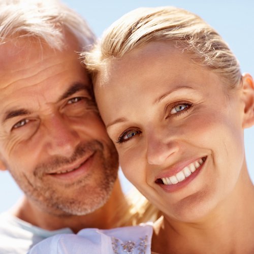 An older couple smiling to illustrate the importance periodontal care on the overall health of your smile.