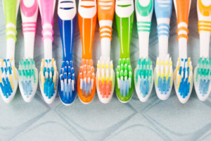 different colored toothbrushes all lined up together