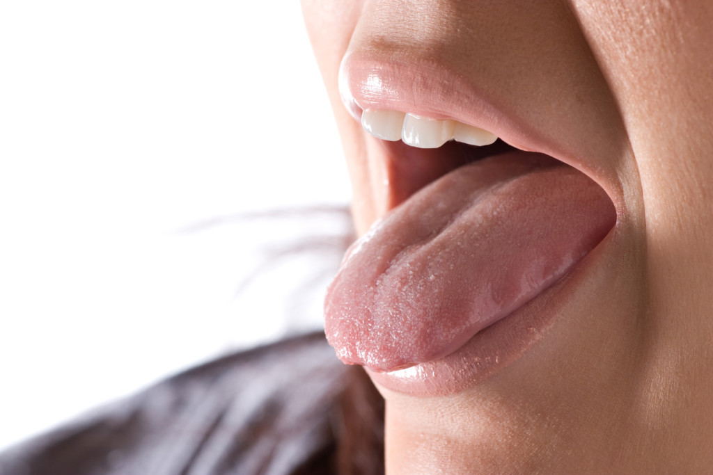Woman sticking out her tongue - how to prevent bad breath