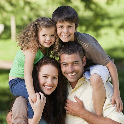 A smiling family of four outside in a park illustrates the speciality services our Harrisonburg Dentists offer.