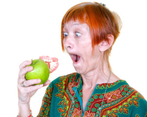 Woman losing her false teeth by biting into an apple