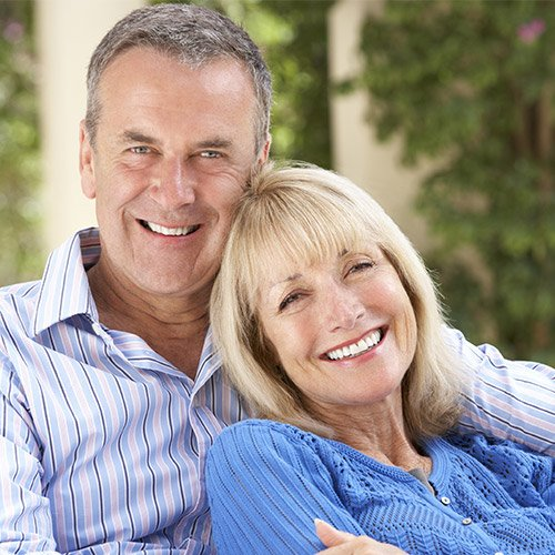 An older couple relaxing outside smile to show the power restorative dentistry can have on your smile.