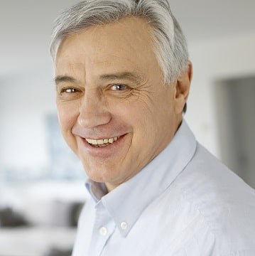 Grey-haired man with healthy smile because of root canal therapy.