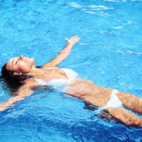 protecting teeth from chlorine - Woman laying in pool