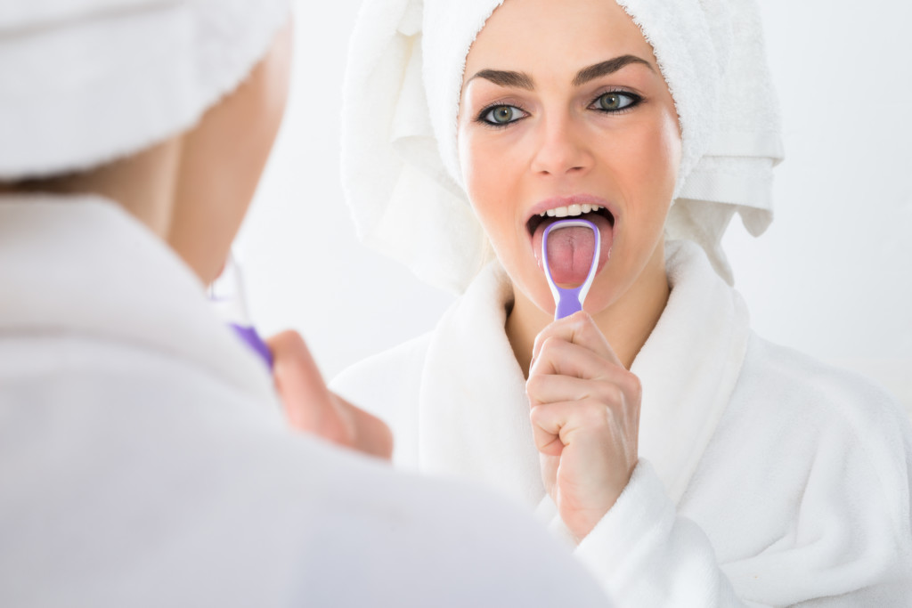 Close-up Of A Woman Looking In Mirror Cleaning Her Tongue - bad breath