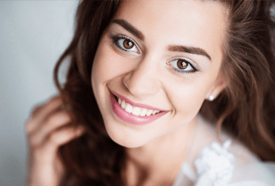 A woman smiles to show how cosmetic dentistry can enhance your smile