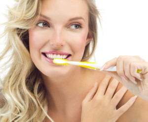 portrait of attractive caucasian smiling woman blond isolated on white studio shot brushing her teeth toothy smile face long hair head and shoulders